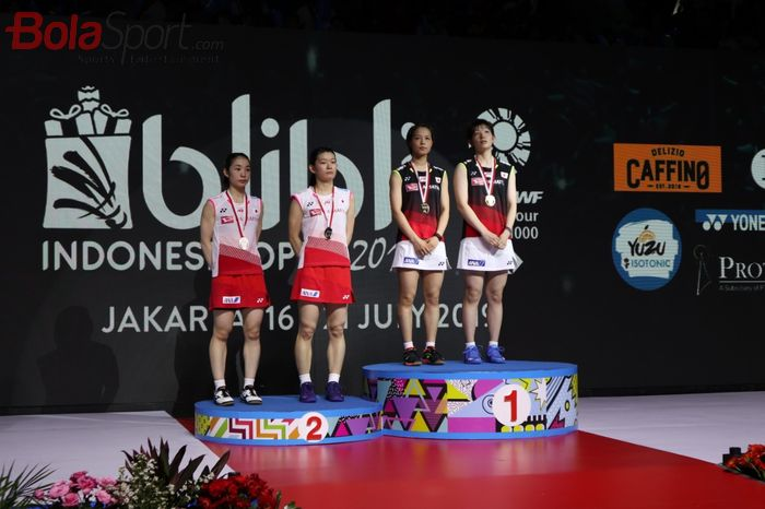 Pasangan ganda putri Jepang, Yuki Fukushima/Sayaka Hirota (kanan, jersey hitam) berpose di podium juara bersama Misaki Matsutomo/Ayaka Takahashi (kiri) seusai final Indonesia Open 2019 di Istora Senayan, Jakarta, Minggu (21/7/2019).