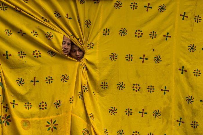 Dari balik tirai berwarna kuning moster, dua biksu mengintip para penari yang tengah tampil dalam perayaan Thimpu Tshechu di Bhutan.