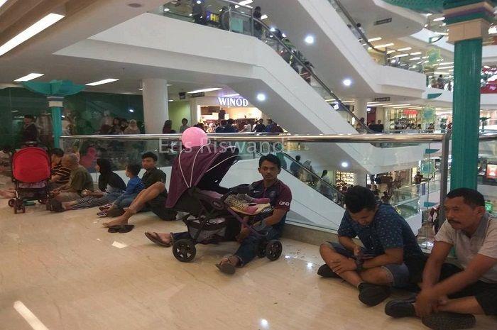 Para pria terduduk di lantai mall untuk menunggu istrinya belanja
