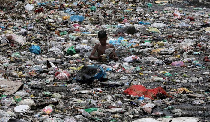 Seorang anak mengumpulkan sampah di New Delhi, India.