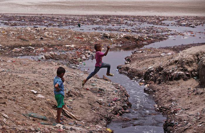 Seorang anak melompati selokan yang dikelilingi sampah di Kanpur, India