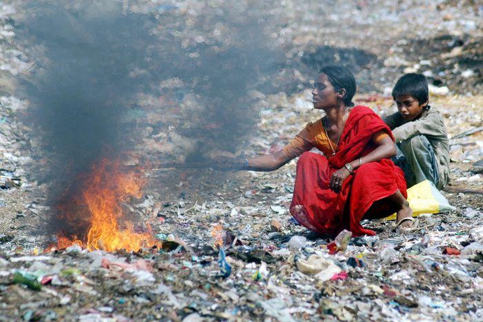 Ibu dan anak membakar sampah di dekat pemukiman kumuh Hyderabad, India.