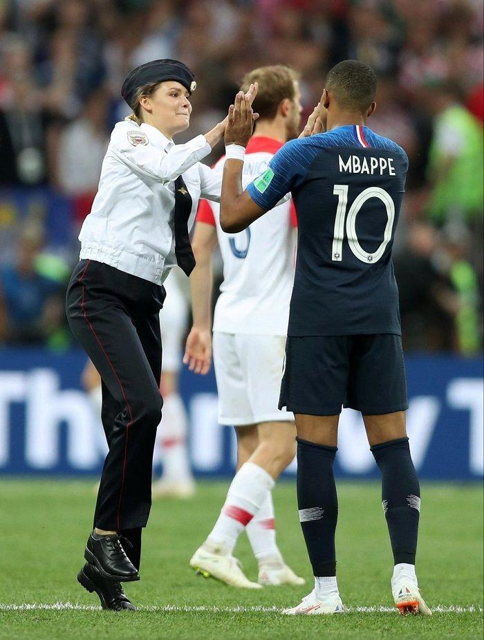 Salah satu anggota Pussy Riot melakukan selebrasi berupa tos dengan pemain Timnas Prancis, Mbappe