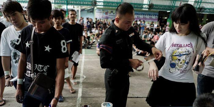 Seorang perwira militer menempatkan selotip di lengan seorang wanita transgender selama draf militer di Bangkok, Thailand, pada 5 April 2017.