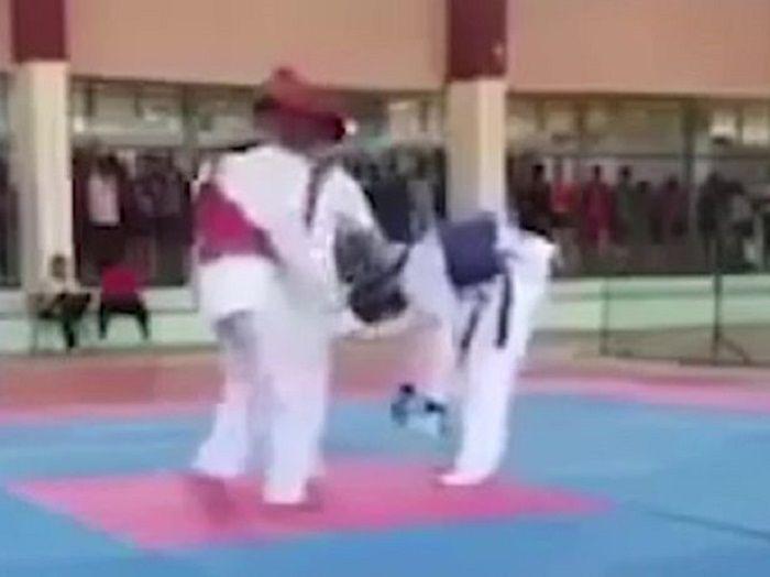 Anak memakai rompi biru membungkuk sebelum terjatuh.
