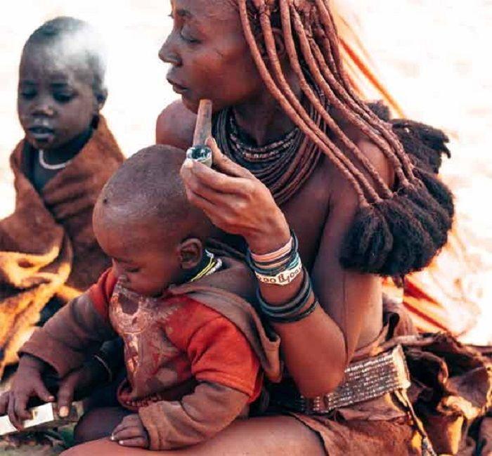 Wanita suku Himba mengolesi tubuhnya dengan oker.