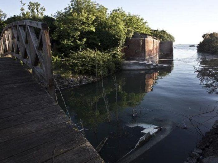Sebuah jembatan menghubungkan pulau tempat bangunan berdiri dengan pulau kecil yang isisnya pohon dan ladang.