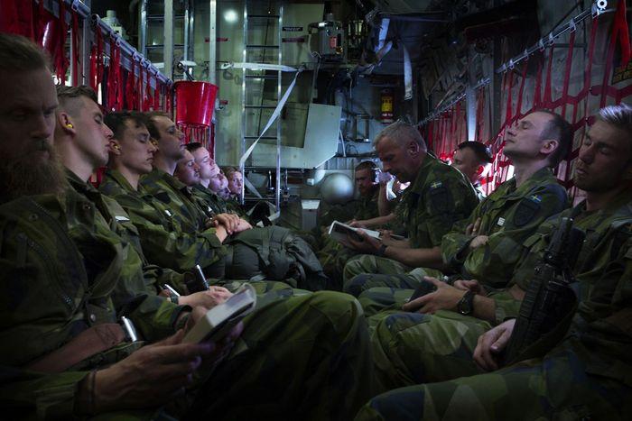 """Tentara membaca dan tidur siang di transportasi dalam perjalanan dari Gotland ke daratan untuk pelatihan pertahanan militer """"Vareld,"""" juga dikenal sebagai """"Spring Fire."""""""