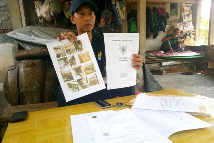 Eko Purnomo (37) tengah memperlihatkan surat sertikat rumah saat ditemui di rumah kontrakannya.(KOMP