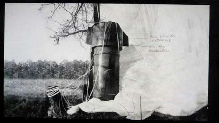 Salah satu bom jatuh dengan parasut mengembang