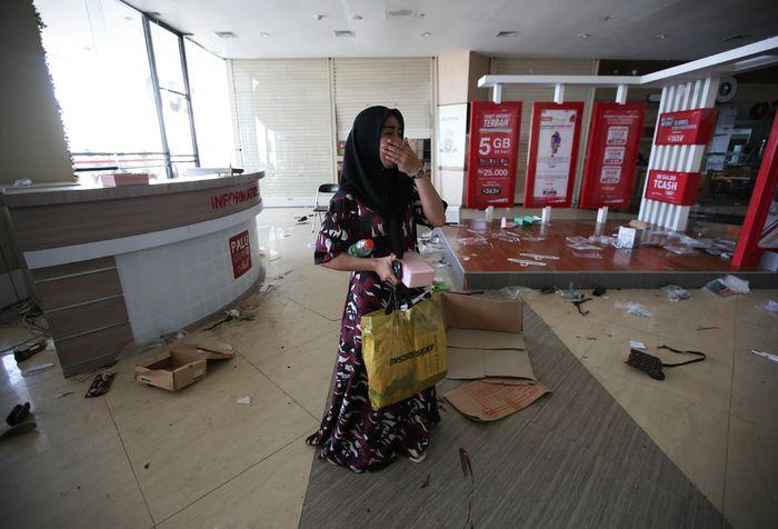 Warga menjarah barang dagangan di Grand Paludi Grand Palu Mall usai gempa bumi di Kota Palu, Sulawesi Tengah, Minggu (30/9/2018). Gempa bermagnitudo 7,4 yang mengguncang Donggala dan Palu mengakibatkan ribuan bangunan rusak dan sedikitnya 420 orang meninggal dunia.