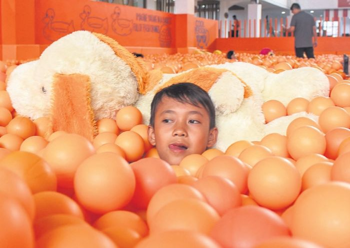 Anak-anak dan orangtua asyik bermain dan bercengkerama dalam rendaman bola-bola plastik di Centrum Million Balls