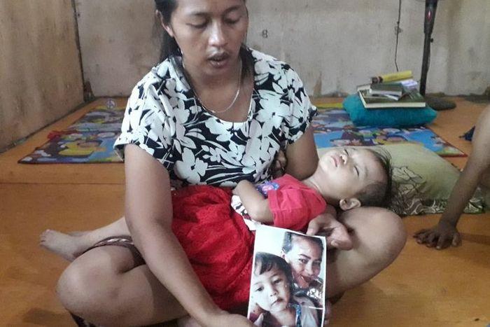Leha menunjukkan potret salah satu anaknya yang meninggal setelah tanpa sengaja terkurung seharian d