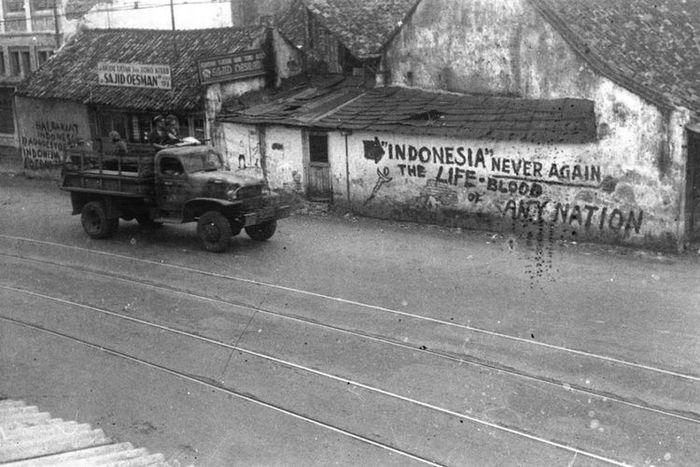 Truk tentara sekutu melintasi dinding-dinding bertuliskan semboyan perjuangan Indonesia