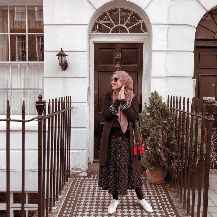 Tampilan chic Zakia Sungkar saat traveling dengan rok dan legging