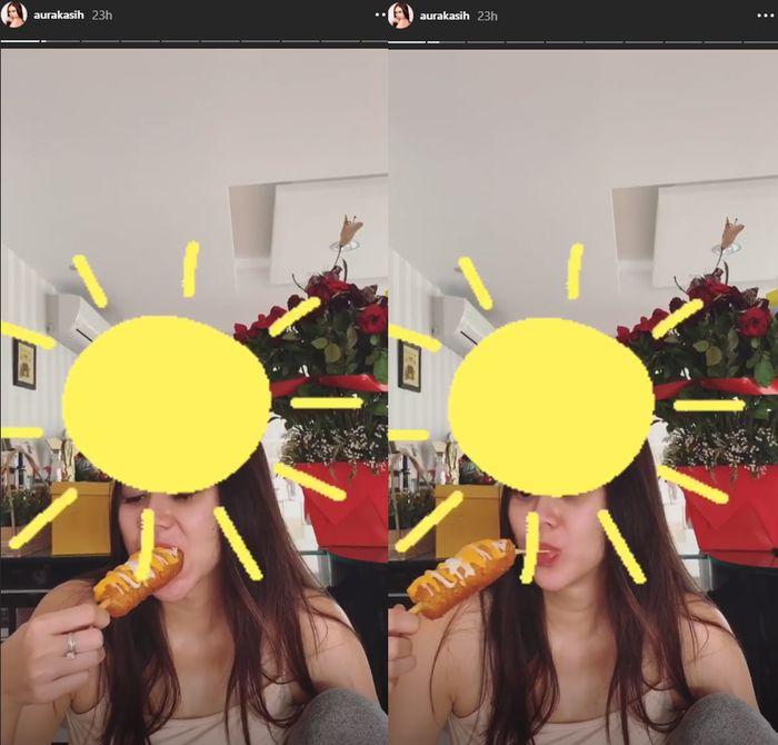 Aura Kasih mengonsumsi corn dog