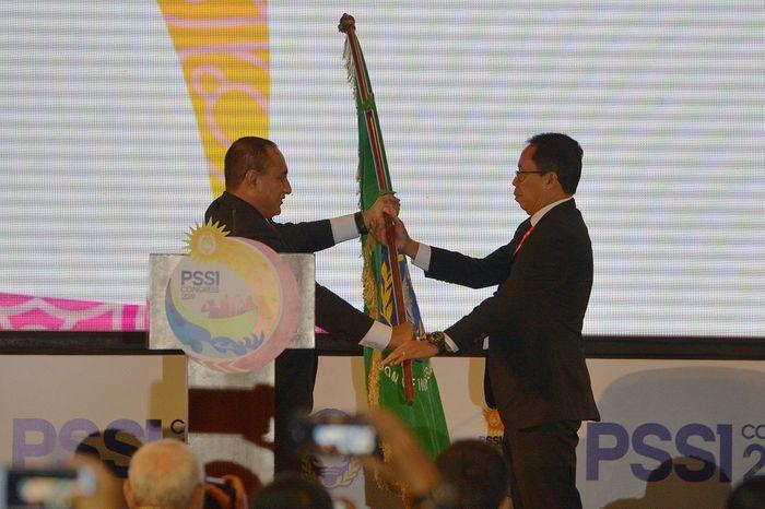 Edy Rahmayadi (kiri) menyerahkan bendera organisasi PSSI kepada Joko Driyono