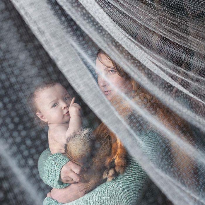 Sepupu fotografer kita, Valentina, memeluk anak bungsunya, Varvara, 10 bulan, selagi bayi itu memainkan bulu rubah.