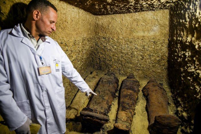 Seorang arkeolog menunjukkan mumi yang mereka temukan di Minya.