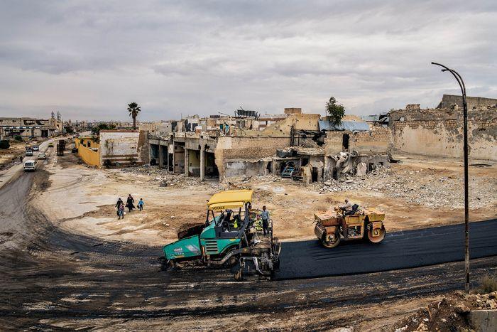 Di dekat bandara internasional, di lingkungan Karm al Jazmati di Aleppo timur, para pekerja membangun jalan untuk menggantikan jalan lama yang telah hancur.