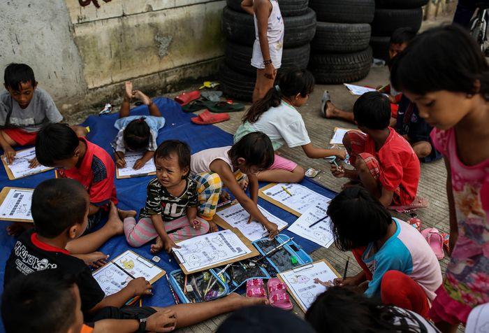 Sejumlah anak-anak saat belajar disebuah terpal yang disediakan oleh Relawan Mentari Senja di kawasan jalan inpeksi sungai banjir kanal barat, kawasan Tanah Abang, Jakarta, Kamis (7/2/2019). Relawan yang terdiri dari pemuda-pemudi yang masih sekolah dan kuliah ini melakukan kegiatan sosial dengan me