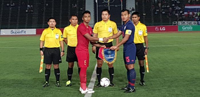 Kapten timnas U-22 Indonesia, Bagas Adi (merah) dan kapten timnas U-22 Thailand, Saringkan Promsupa sali berjabat tangan sebelum final Piala AFF U-22 2019, 26 Februari 2019.