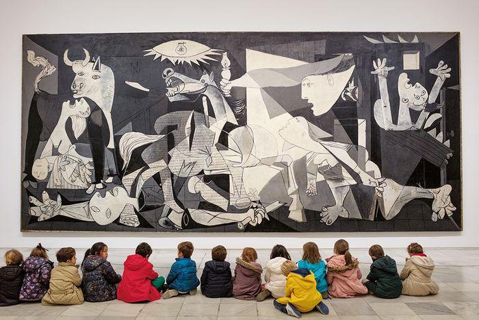 """Di museum Reina Sofía di Madrid, anak sekolah mengunjungi lukisan ikonik Picasso, """"Guernica,"""" yang menampilkan kematian dan penderitaan setelah pengeboman kota Basque tersebut pada 1937. Meskipun terinspirasi oleh Perang Saudara Spanyol, gambar ini mewakili penderitaan universal, di mana pun atau kapan pun terjadinya."""