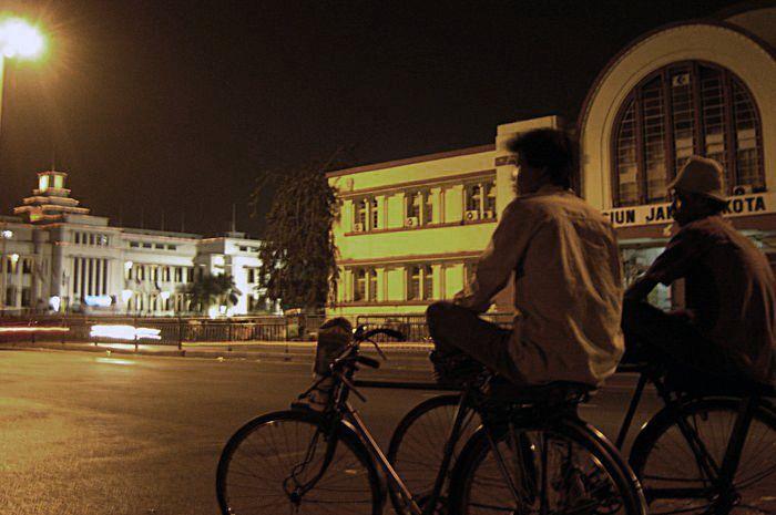 Dua tukang ojek sepeda menanti pelanggan di depan pintu selatan Stasiun Jakarta Kota.