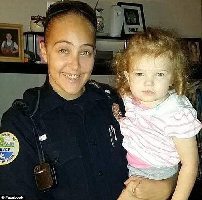 Cassie Baker (29) saat masih berseragam polwan tengah menggendong mendiang putrinya.