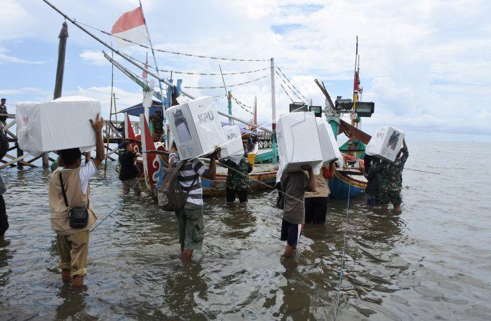 Petugas membawa logistik pemilu menyeberangi laut.