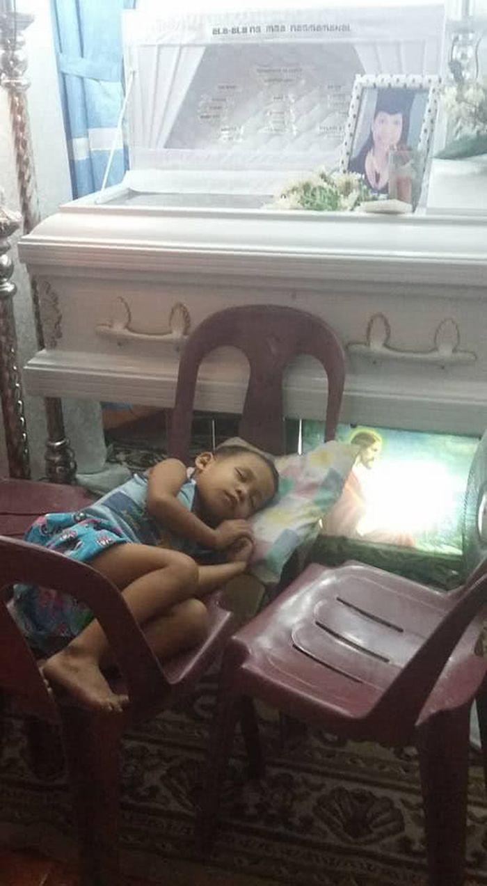Khayne Kheian tidur di dekat peti mati ibunya.