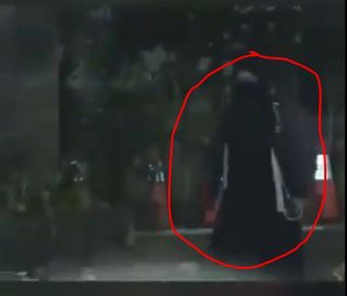 Sosok wanita berbaju hitam yang mendekati barisan polisi.