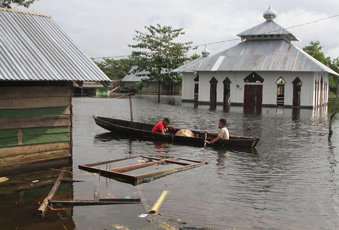 Dua orang anak berada di atas perahu menerobos banjir sejak dua pekan lalu di Desa Laloika, Kecamatan Pondidaha, Konawe, Sulawesi Tenggara, Minggu (9/6/2019). Banjir bandang merendam beberapa kecamatan di Kabupaten Konawe akibat meluapnya Sungai Konaweha disebabkan intensitas hujan tinggi sementara