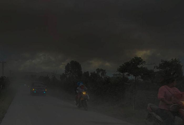 Pengendara melintasi jalan yang tertutup debu vulkanik dampak erupsi Gunung Sinabung, di Karo, Sumatera Utara, Minggu (9/6/2019). Gunung Sinabung berstatus Siaga (Level III) kembali mengalami erupsi dengan tinggi kolom abu mencapai 7.000 meter dan menyebabkan sejumlah desa tertutup debu vulkanik.