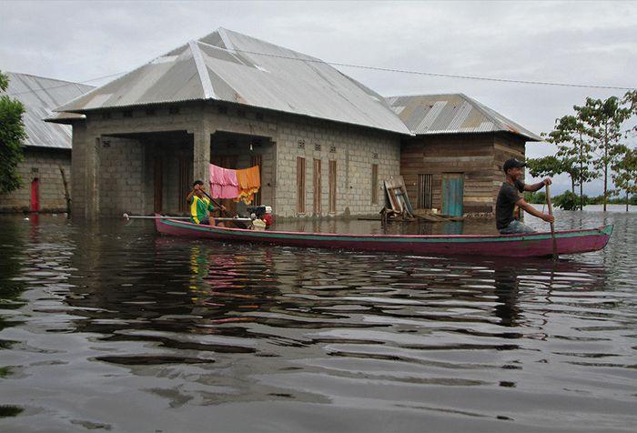 Warga berada di atas perahu menerobos banjir sejak dua pekan lalu di Desa Laloika, Kecamatan Pondidaha, Konawe, Sulawesi Tenggara, Minggu (9/6/2019). Banjir bandang merendam beberapa kecamatan di Kabupaten Konawe akibat meluapnya Sungai Konaweha disebabkan intensitas hujan tinggi sementara BPBD Kona
