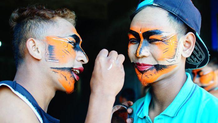 Dua orang penari Jaran Kepang Kolaborasi saling membantu merias wajah.