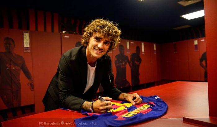 Antoine Griezmann menandatangani seragam anyarnya di FC Barcelona.