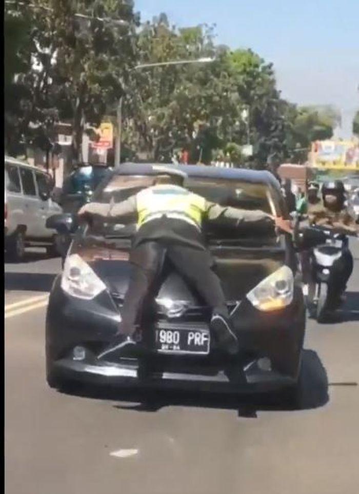 Polisi yang sampai bertahan di kap mobil sang pelanggar