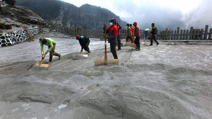Beberapa petugas membersihkan jalanan yang memutih tertutup abu vulkanik
