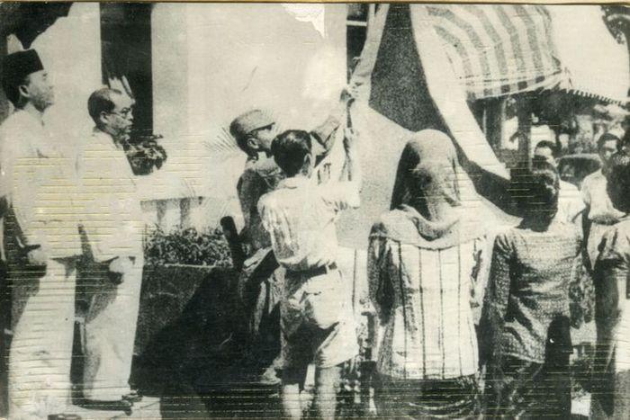 Upacara penaikan bendera sang merah putih di halaman gedung pegangsaan timur 56 (Gedung Proklamasi). Tampak antara lain Bung Karno, Bung Hatta, Let,Kol. Latief Hendraningrat (menaikkan bendera) Ny. Fatmawati Sukarno dan Ny.S.K Trimurti.