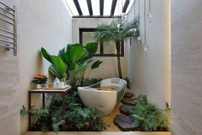 Atap terbuka dengan berbagai jenis tanaman memberi suasana hutan alami yang sejuk di kamar mandi.