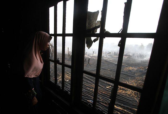 Warga melihat kebakaran lahan gambut dari balik jendela rumah di desa Pengayuan, Banjarbaru, Kalimantan Selatan, Sabtu (14/9/2019). Kebakaran lahan gambut di kawasan tersebut mengakibatkan satu tempat usaha warga dan sebagian dinding rumah warga ikut terbakar.