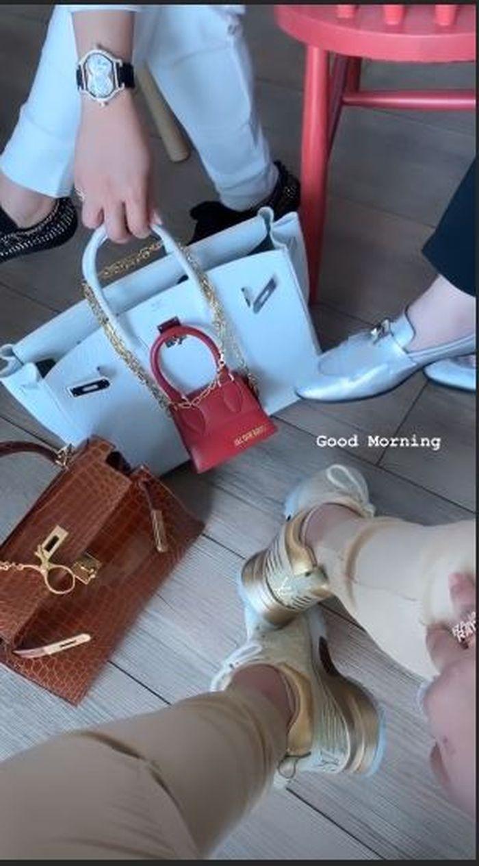 Syahrini melengkapi tas Hermes dengan tambahan tas mungil berwarna merah dari brand Jacquemus