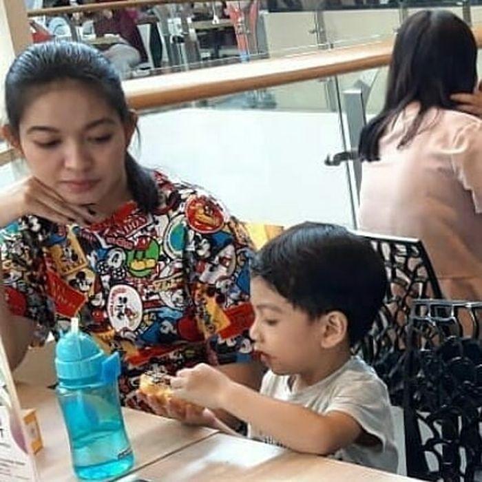 Potret sederhana Selvi Ananda yang memakai kaus mickey mouse saat temani Jan Ethes makan donat di food court