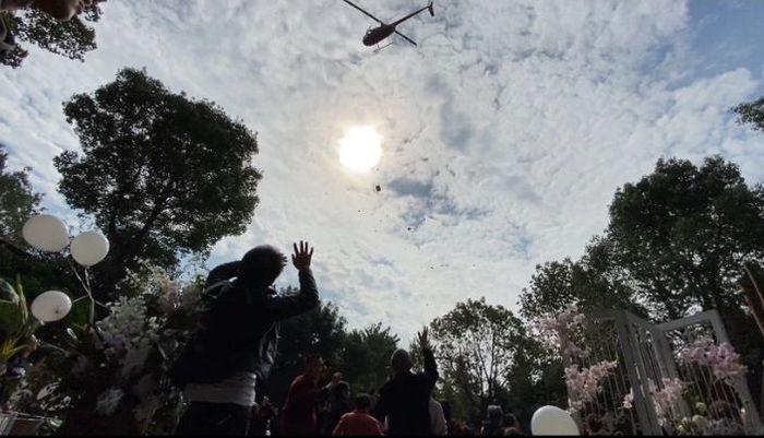 Helikopter tersebut menaburkan bunga di atas pernikahan itu.
