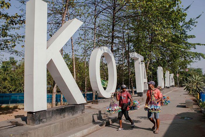 Dua orang pedagang berjalan di landmark Kota Bekasi.