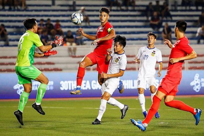 Kapten timnas U-22 Singapura, Irfan Fandi, saat berebut bola dengan pemain Laos pada cabor sepak bola SEA Games 2019. (FA SINGAPORE)