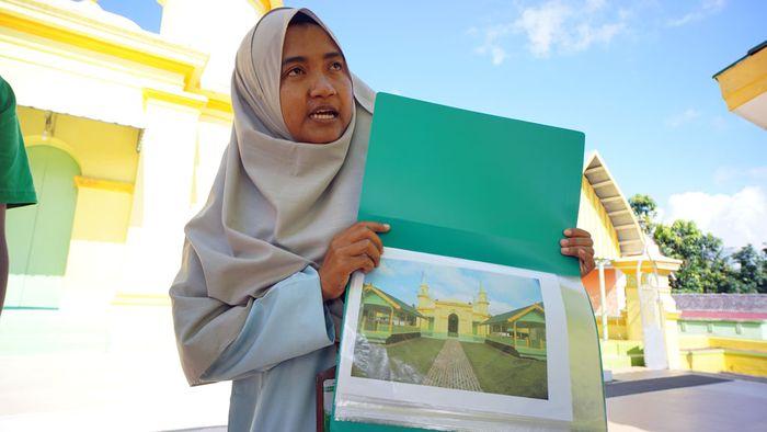 Nurfatilla Afidah, intepreter Tur Masjid Raya Sultan Riau, menunjukkan foto Masjid Sultan Riau Penyengat saat dirinya masih kecil.