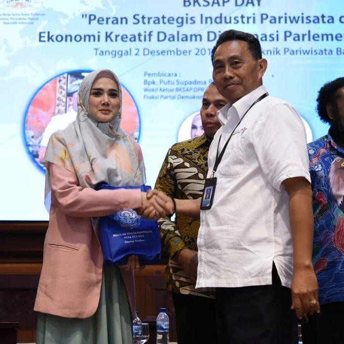 Tampil santun saat menerima kenang-kenangan setelah selesai bertugas menjadi pembicara seminar di depan mahasiswa