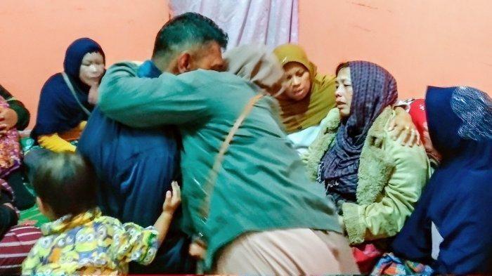 Aiptu Rukur Sidabutar (jaket hitam) dipeluk oleh keluarga saat di rumah duka, Selasa (17/12/2019) malam. Tampak pula istri Aiptu Rukur tersandar di bahu keluarganya sambil menangis tersedu-sedu.